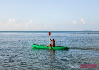 Woman kayaking at sunset, Ko Samui, Thailand