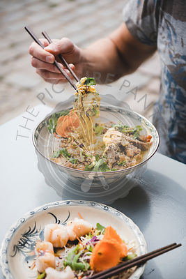 Man eating vietnamese noodle curry with duck with chopsticks