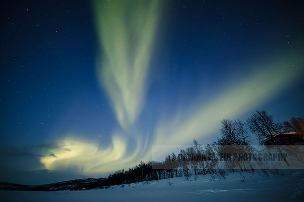 Northern lights above Finnish cottages in Lapland
