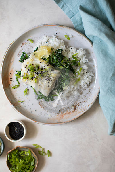 Baked fish fillet with wilted spinach and green beans on a bed of rice.