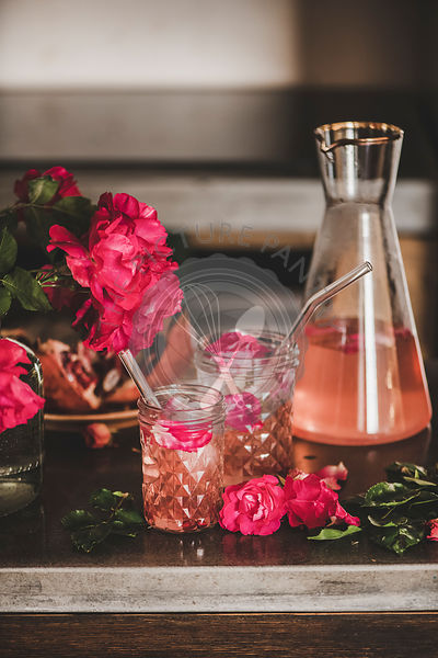 Rose lemonade with ice cubes and petals over kitchen counter