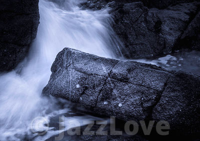 Wave splashing on dark and wet rocks.