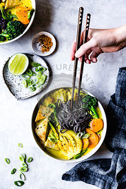 Thai curry with black rice noodles, tofu, carrot, broccolini, bok choy, cauliflower, lime, scallions