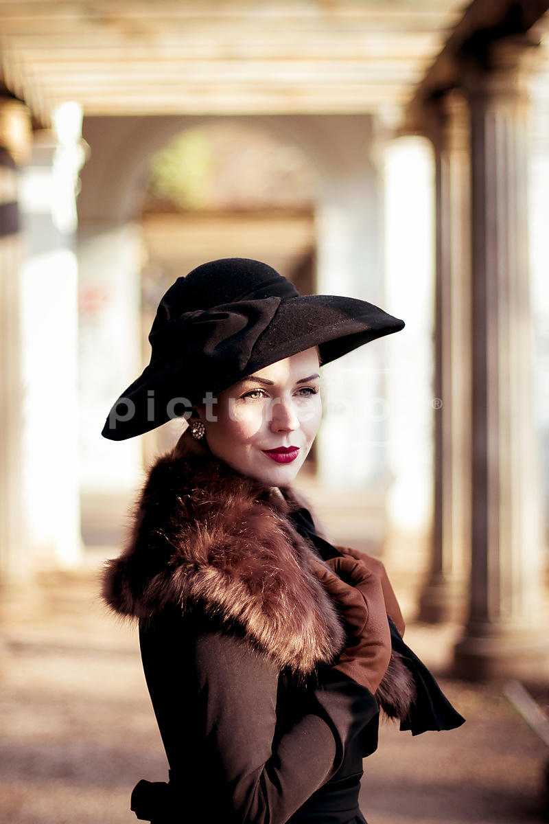 A vintage woman, in a fur, coat and hat.