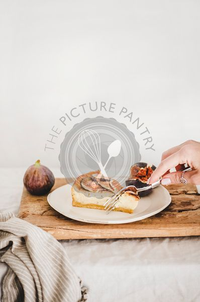 Hand of woman eating homemade gluten free fig cheesecake