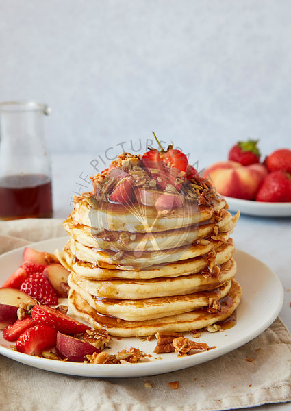 Stack of American Pancakes served with Stawberries, Peaches, Granola and Maple Syrup