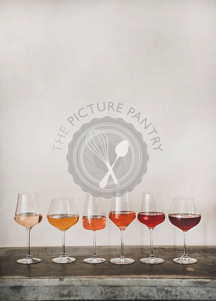 Various shades of Rose wine in stemmed glasses in line