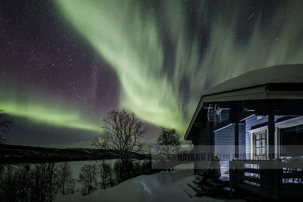 Tourist sitting in front of his typical Finnish cottage watching the northern lights dance in the sky