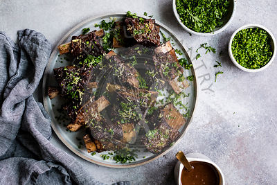 Roasted beef ribs with chopped parsley and chives on a plate.
