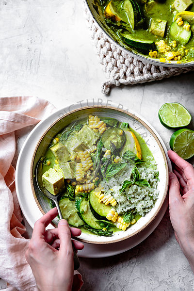 Bowl of thai green curry with rice and tofu.