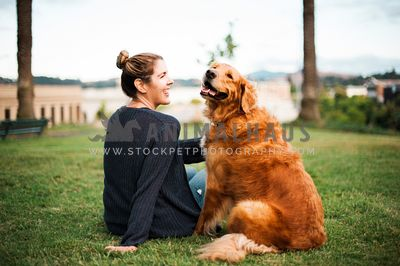 A woman smiling and patting her golden retriever on the grass