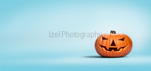 An unlit Halloween Jack O Lantern isolated on a widescreen pale blue background