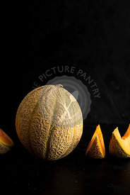 Whole melon with melon slices over black background