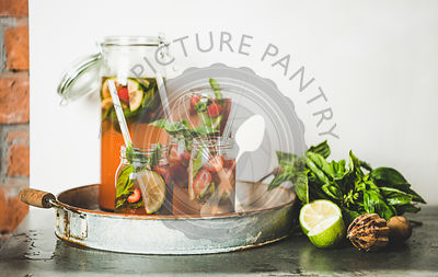 Fresh strawberry and basil lemonade in glass jars, copy space