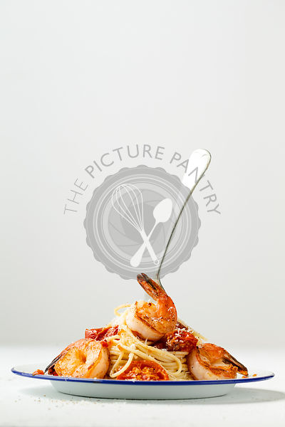 Spaghetti with pan seared prawns, oven roasted tomatoes and parmesan, on an enamel plate with a fork. Light background.