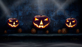 Three lit halloween Jack O Lanterns on the left, right and centre on a stone plinth  at night with many unlit lanterns and sm...