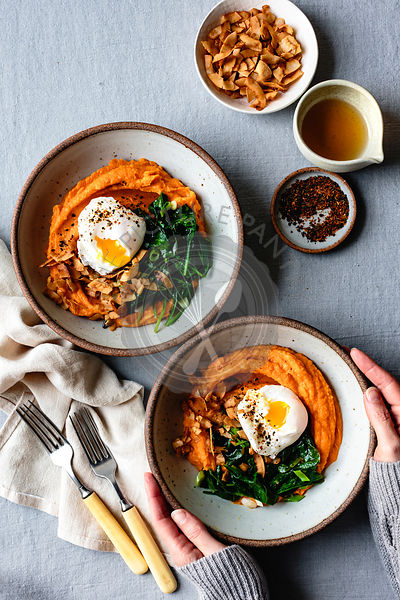 Hands holding a sweet potato breakfast bowl.