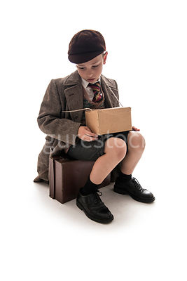 A 1940's boy sitting on a suitcase – shot from mid level.