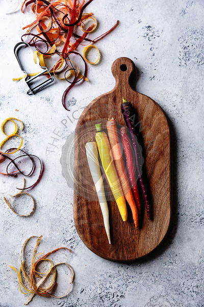 Rainbow carrots on a wooden cutting board.