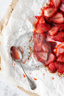 Roasted Strawberries On Parchment Paper Drizzled In Syrup And Juice