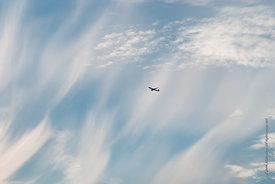 #73943,  Jet aircraft passing below cirrus clouds driven by high winds above southern England.