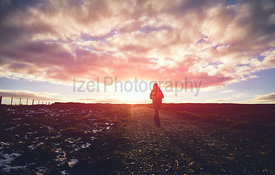 The silhouette of a hiker walking into the sunset across a moorland trail.