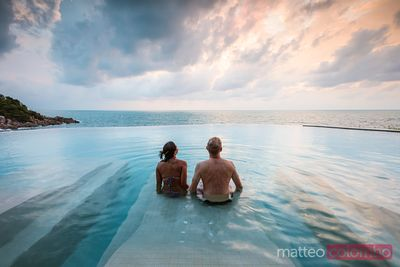 Tourist couple in an infinity pool at sunset, Ko Samui