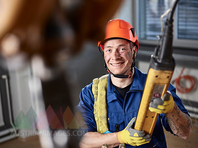 Industrial worker using hand control of indoor crane