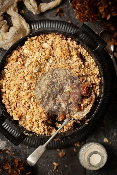 Pear and chocolate crumble partially served from a cast iron skillet