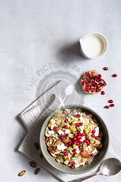 Bowl of breakfast cereal, seeds, nuts and pomegranate seeds; with copyspace.