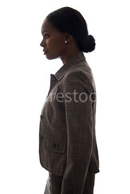 A tough woman, standing and looking around, in semi-silhouette – shot from eye level.