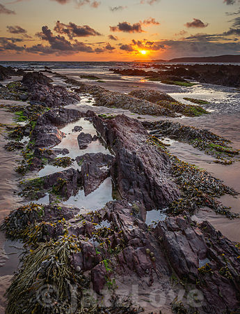 Sunset on scenic rocky beach in Freshwater West, South Wales, UK.