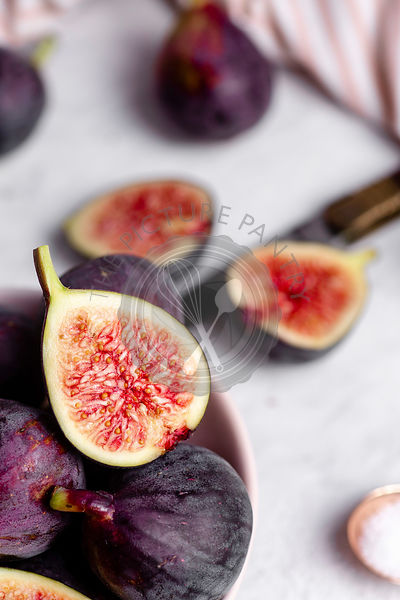 Close up of a halved fig, sitting on top of other purple figs in a bowl with a knife, striped napkin, and white marble counte...