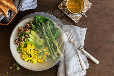 Breakfast bowl with scrambled  tofu and vegetables in stoneware bowl on laid wooden table with copy space