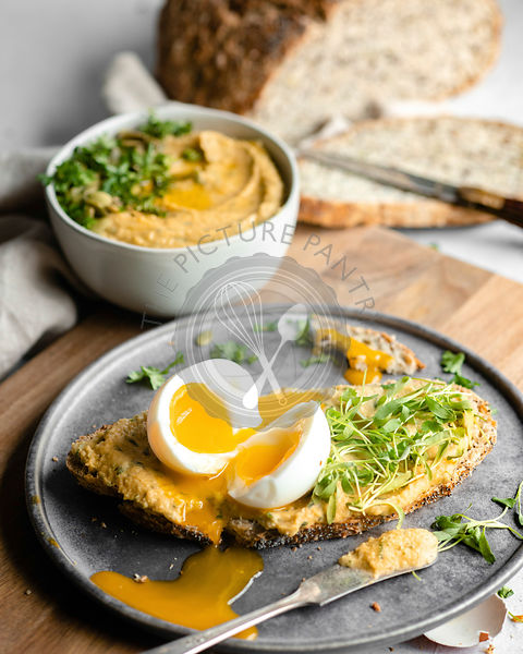 A soft boiled egg, cut in half on a thin slice of bread covered with hummus and greens on a silver plate sitting on a wood cu...