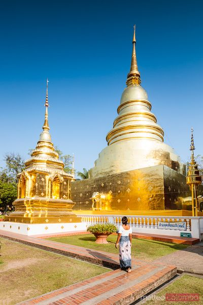Woman looking at golden stupas, Chiang Mai, Thailand