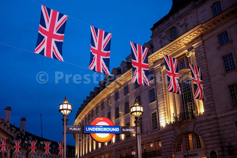Five Union Jack flags strung across Regent Street with illuminated Underground sign  at twilight