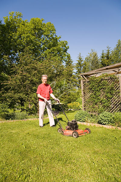 Senior man using lawnmover