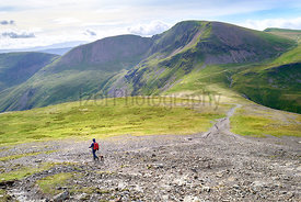 A hiker from Hopegill Head towards Coledale Hause, with Crag Hill and Sail in the distance. The Lake District, England, UK.