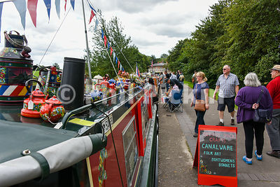People looking at narrowboats moored along the towpath.