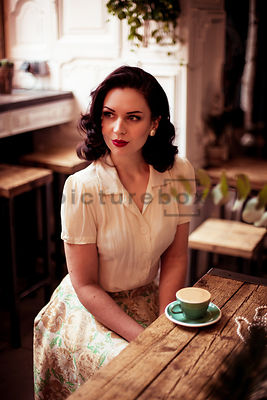 A vintage woman drinking coffee.