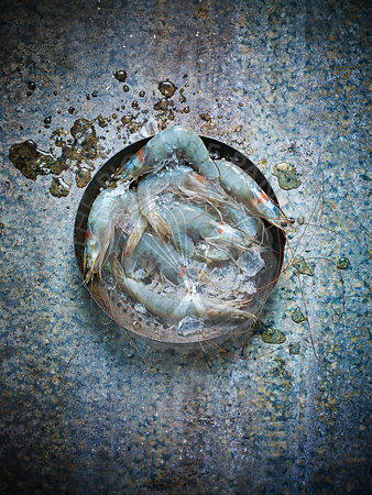 Raw prawns in a collander against a blue background