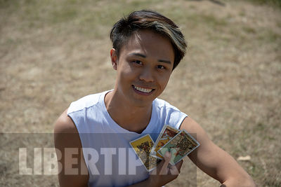 ONE YOUNG CHINESE GAY MAN DOING TAROT CARDS OUTDOORS.