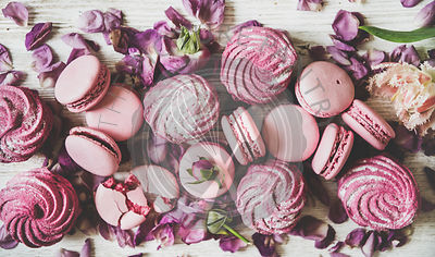 Sweet pink macarons, marshmallows and spring flowers and petals