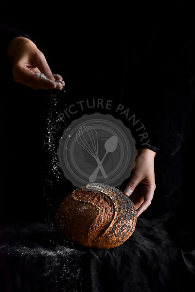 Sourdough Boule on a dark background with flur being sprinkled from hands