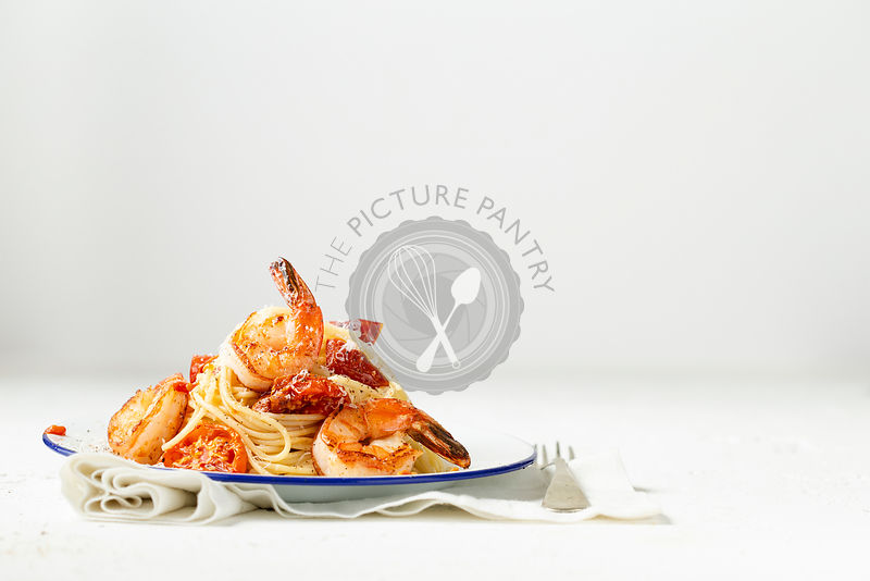 Spaghetti with pan seared prawns, oven roasted tomatoes and parmesan, on an enamel plate with a fork and linen. Light backgro...