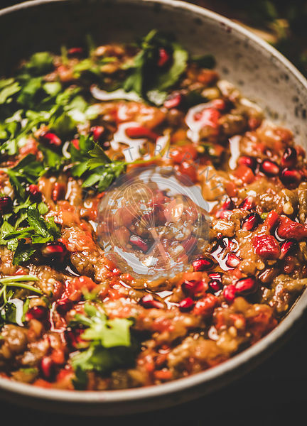 Babaganoush cold dip seasoned with parsley, pomegranate seeds in pan