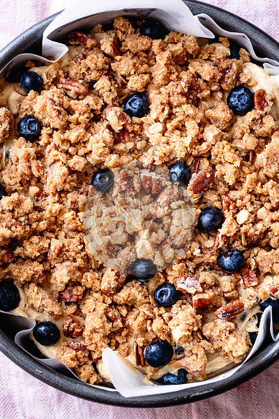 Closeup view of a prepared blueberry coffee cake in a paper lined baking tin.