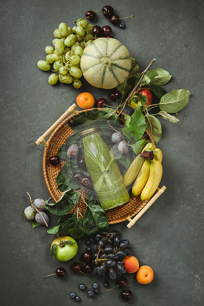 Flat-lay of organic fruits and berries and Freshly blended fruit smoothie on green concrete background. Top view. Local farme...