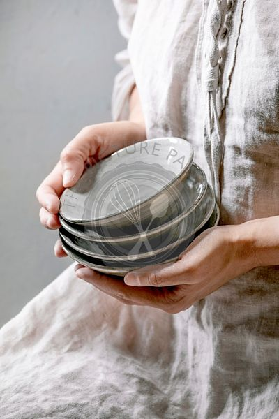 Woman in cotton dress hold in hands set of empty craft ceramic bowls cover by grey texture glaze.